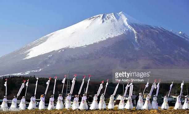 People wearing white clothes holding threemeterlong 'Kenzao' rods march on at the skirt of Mount Iwatesan during the Hirakasa Hadaka Mairi on January...