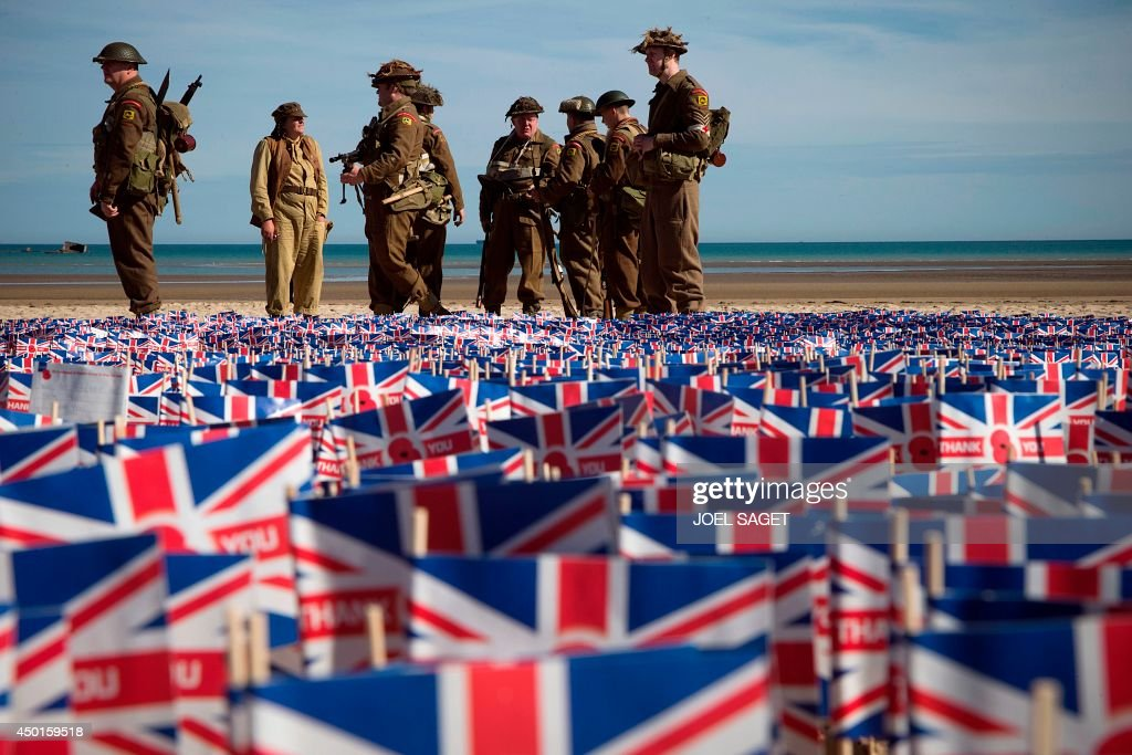 People wearing WWII British uniforms stand in front of