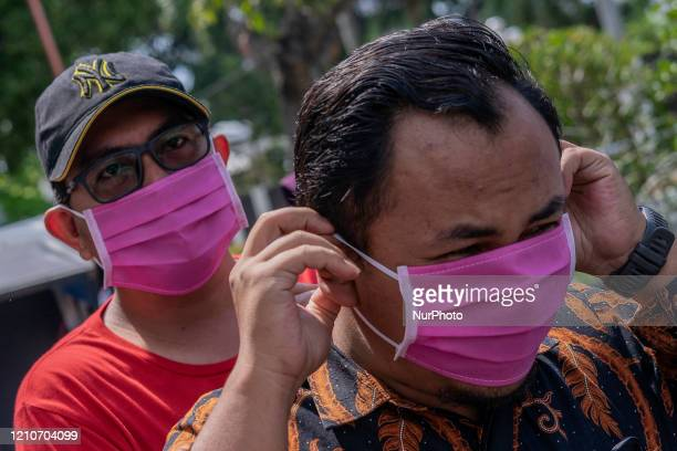 People wears a face masks given by Anti Narcotics Agency as a preventive measure spread of COVID19 in Lhokseumawe Aceh Indonesia on April 22 2020...