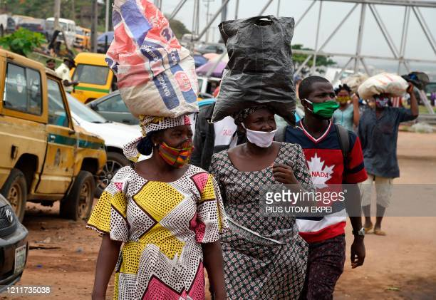 People wears face masks in compliance with state directive to curb the spread of COVID-19 coronavirus at Ojodu-Berger in Lagos, on May 4, 2020. -...
