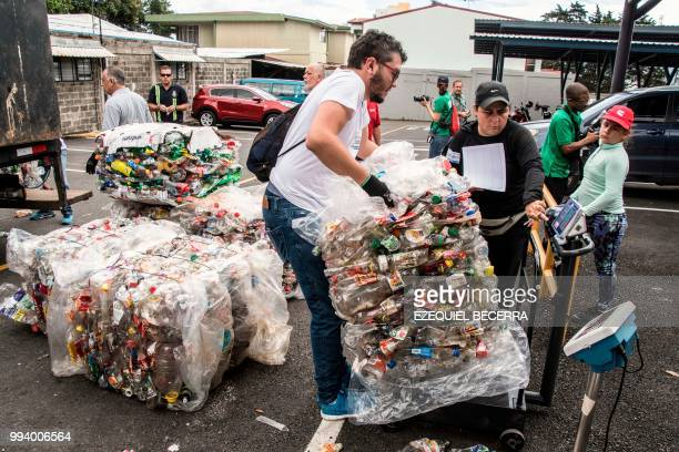 People weigh plastic bottles as they help collect 25 tons of them for recycling in eight hours in order to set a Guinness World Record in San Jose on...