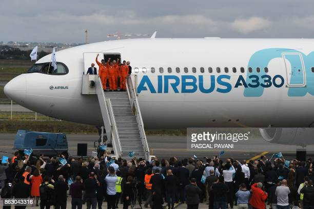 People welcome pilots at the end of the first flight of the new Airbus A330 on October 19 at the ToulouseBlagnac airport near Toulouse / AFP PHOTO /...