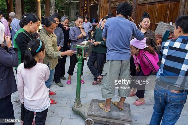 People were weighing a man on scale which would weigh piggy with great joy at Zhaoxing Dong village,Guizhou.