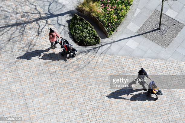People wheeling prams keep their distance as they walk in south London on March 24 2020 after Britain ordered a lockdown to slow the spread of the...