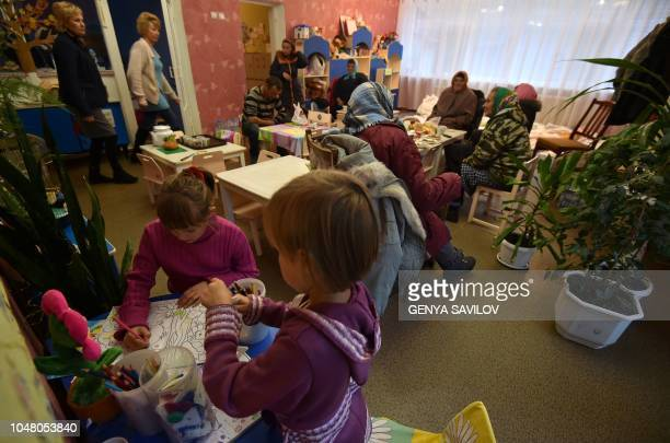 People which were evacuated after arms depot explosion near the town of Ichnya north of Ukraine more than 170 kilometres from Kiev on October 9 sit...