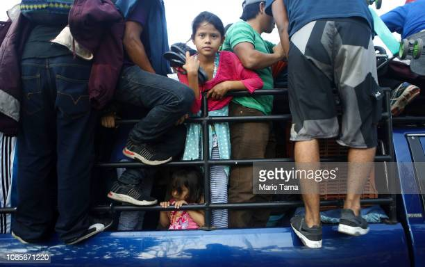 People who are a part of a caravan of Central American migrants prepare to ride in the back of a pickup truck after the driver offered to give them a...