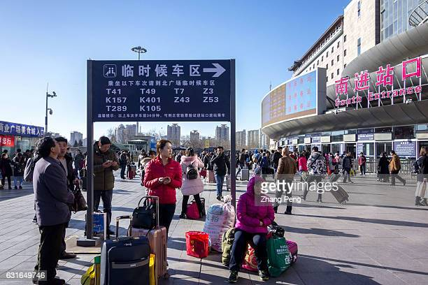 People who are ready to hurry home by train and spend the Spring Festival with their families arrives ahead of time and waits on the square of...