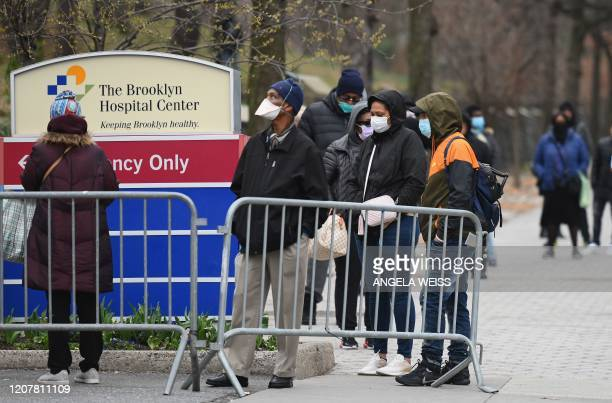 People who believe they have COVID19 and who meet the criteria wait in line to be prescreened for the coronavirus outside of the Brooklyn Hospital...