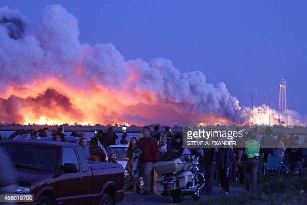People who came to watch the launch walk away after an unmanned rocket owned by Orbital Sciences Corporation exploded October 28 2014 just seconds...
