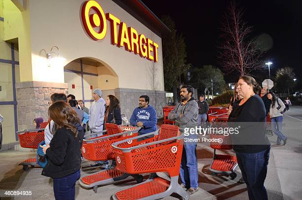 CONTENT] People who didn't want to wait in line on Thanksgiving for Target to open at 8 pm for an early Black Friday sale stand with their shopping...