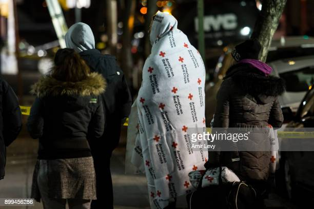 People who evacuate from their house after a fatal major house fire on Prospect avenue on December 29 2017 in the Bronx borough of New York City Over...