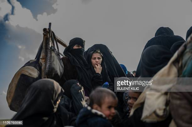 TOPSHOT People who fled the Islamic State group's last holdout of Baghouz in Syria's northern Deir Ezzor province wait in the back of a truck on...