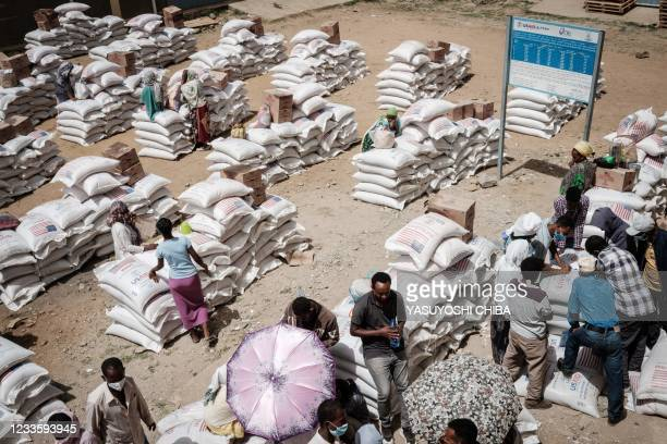People, who fled the violence in Ethiopia's Tigray region, gather to receive food during a food distribution organised by the local NGO Relief...