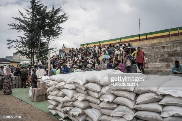 People who fled the war from May Tsemre, Addi Arkay and Zarima gather around in a temporarily built internally displaced people camp to receive their...