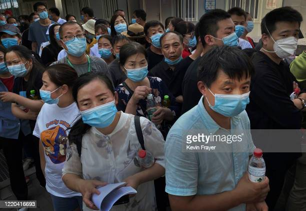 People who have had contact with the Xinfadi Wholesale Market or someone who has, line up for a nucleic acid test for COVID-19 at a testing center on...