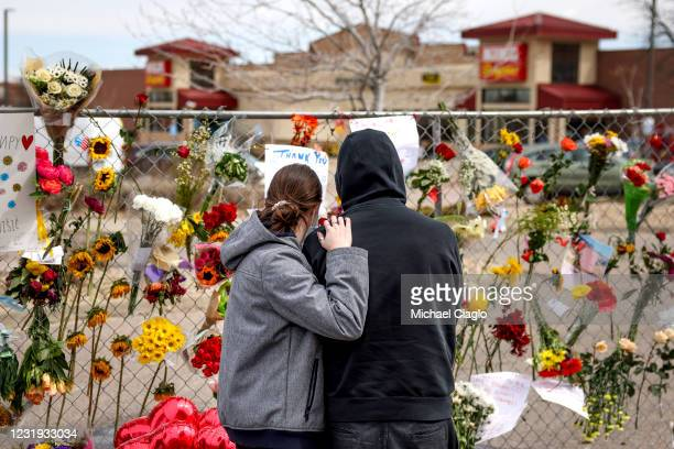 People who knew shooting victim Neven Stanisic comfort each other at a makeshift memorial outside a King Soopers grocery store on March 25, 2021 in...