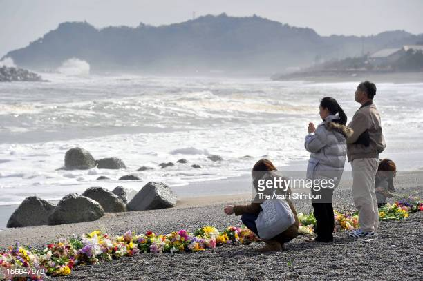 People who lost their families and friends by the tsunami followed by the strong earthquake offer flower bunches at the Hisanohama coast on March 11...