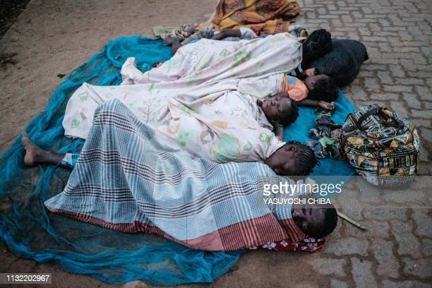 People who lost their home by the cyclone Idai sleep on a street as they stay in shelter in Buzi Mozambique on March 23 2019 The death toll in...