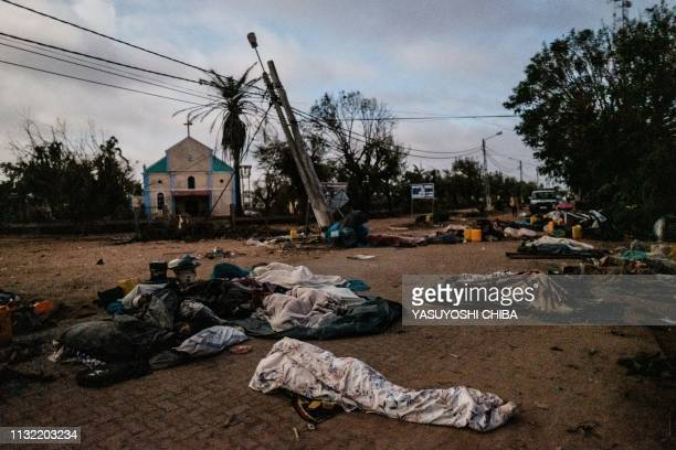 TOPSHOT People who lost their home by the cyclone Idai sleep on a street as they stay in shelter in Buzi Mozambique on March 23 2019 The death toll...
