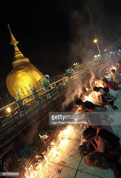 People who pray at night with candles near the golden rock.