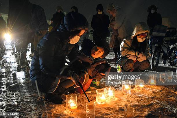 People who suffer the 2011 earthquake and subsequent tsunami commemorate the victims of the Great Hanshin Earthquake during the memorial event to...