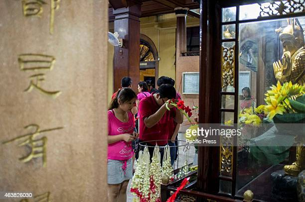 People who visited a Buddhist temple during the Chinese New Years Eve say their prayers in front of a Buddha statue with incense and flowers as...