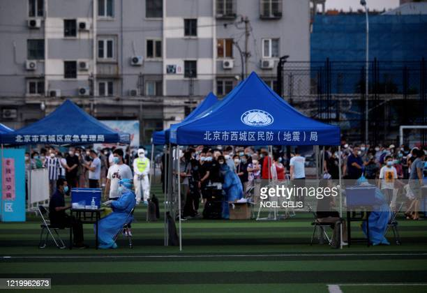People who visited or live near Xinfadi Market queue for a swab test at Guang'an Sport Center in Beijing on June 14 2020 The domestic COVID19...