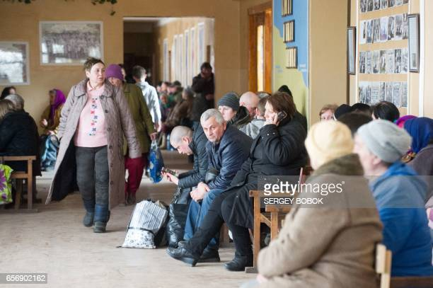 People who were evacuated due to a fire raging at a military munitions depot near the city of Balakliya wait on March 23 2017 at a school in the...