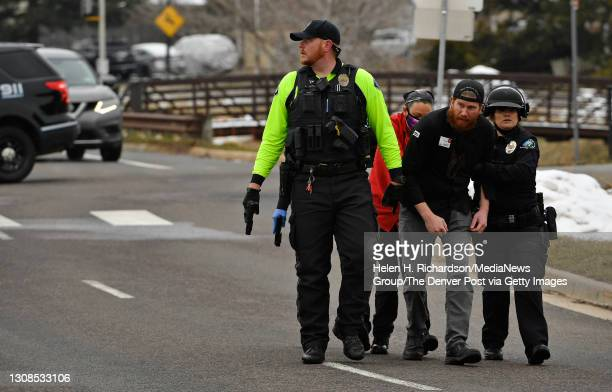 People who were inside the King Soopers are escorted down the street by Boulder Police after being taken out of the supermarket after a shooting in...