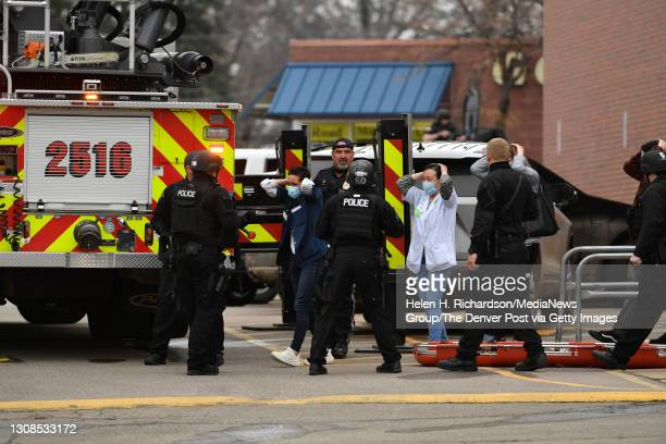 People who were inside the King Soopers come out of the store with their hands on their heads are escorted by police and SWAT members after a...