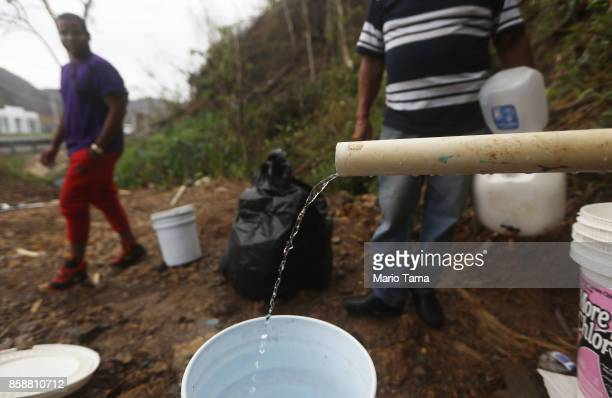 People whose homes no longer have running water wait to fill jugs with spring water flowing from a mountain more than two weeks after Hurricane Maria...