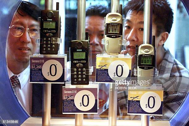 People windowshop for free mobile phones at a streetside display by one of Hong Kong's six mobile telephone network operators 01 March in Hong Kong A...