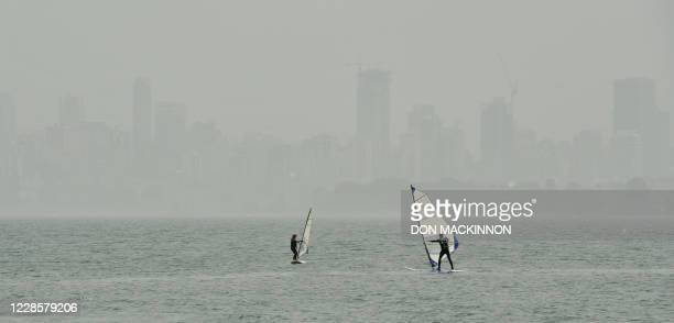 People windsurf in Burrard inlet as the heavy smog and smell of wood smoke hangs over the Vancouver, British Columbia skyline in the background on...