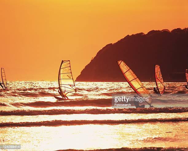 people windsurfing in the sea, shonan, kanagawa prefecture, japan, side view, toned image - zushi kanagawa stock photos and pictures