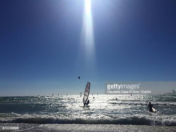 People Windsurfing On Sea Against Sky On Sunny Day