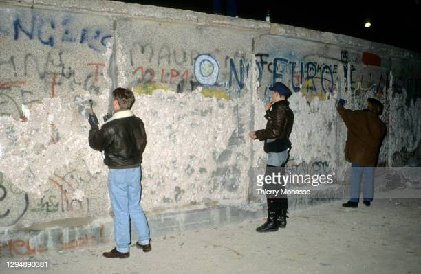 People with a chisel and sledgehammer participate in the destruction of the Berlin Wall near by the Brandenburg Gate, as they celebrate the first New...
