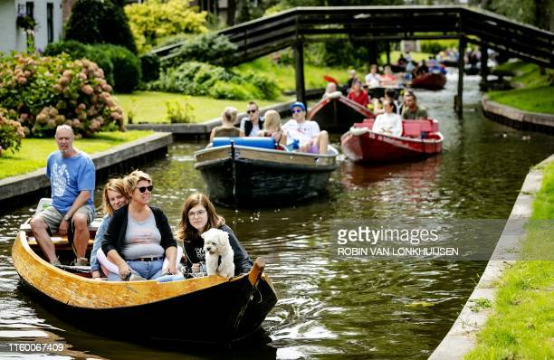 People with a dog take a boat ride on a river in Giethoorn, a well-known destination for tourists and day-trippers, on August 6, 2019. / Netherlands...