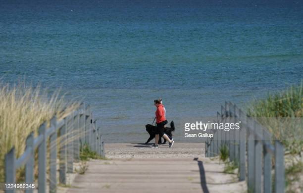 People with a dog walk on mostly-deserted Prora beach on Ruegen Island during the coronavirus crisis on May 14, 2020 in Prora, Germany....