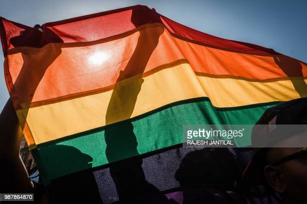 People with a rainbow flag take part in the annual Gay Pride Parade as part of the threeday Durban Pride Festival on June 30 2018 in Durban