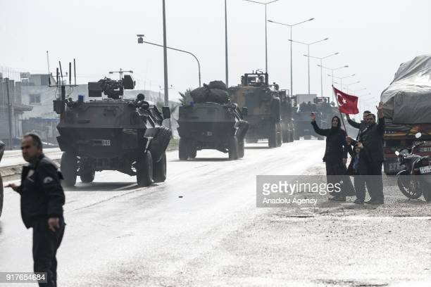 People with a Turkish flag greet the convoy of armoured military vehicles while they are being transported to support the units at border within the...