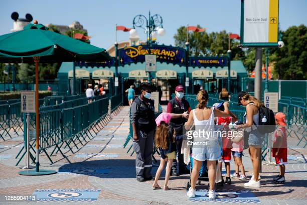 People with annual passes wearing protective face masks arrive to visit Disneyland Paris on July 13, 2020 in Marne-la-Vallee, near Paris, France....