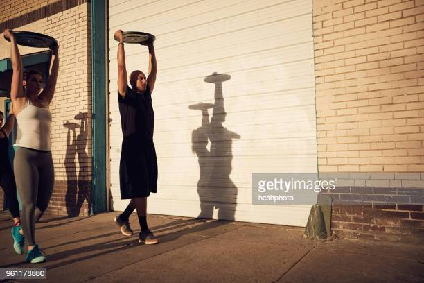 people with arms raised carrying weights equipment - heshphoto stock pictures, royalty-free photos & images