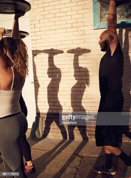people with arms raised carrying weights equipment, side view - heshphoto stockfoto's en -beelden