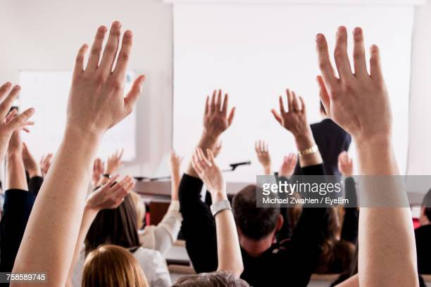 People With Arms Raised In Lecture Hall During Seminar