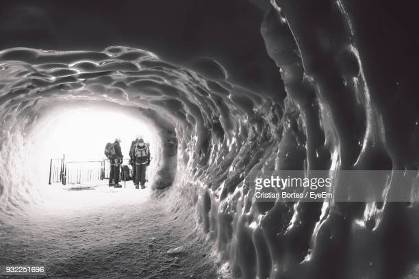 People With Backpacks Standing At Entrance Seen Through Ice Cave
