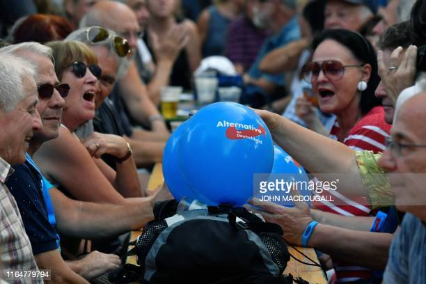 People with balloons attend an election rally of the far-right party Alternative for Germany in Koenigs Wusterhausen, eastern Germany on August 30,...