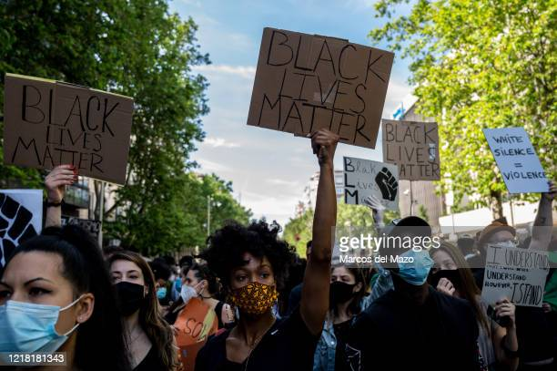 People with Black Lives Matter placards wearing protective face masks during a demonstration in front of the US Embassy protesting against the death...