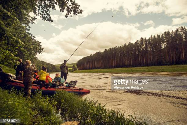 people with boat fishing on riverbank - flussufer stock-fotos und bilder