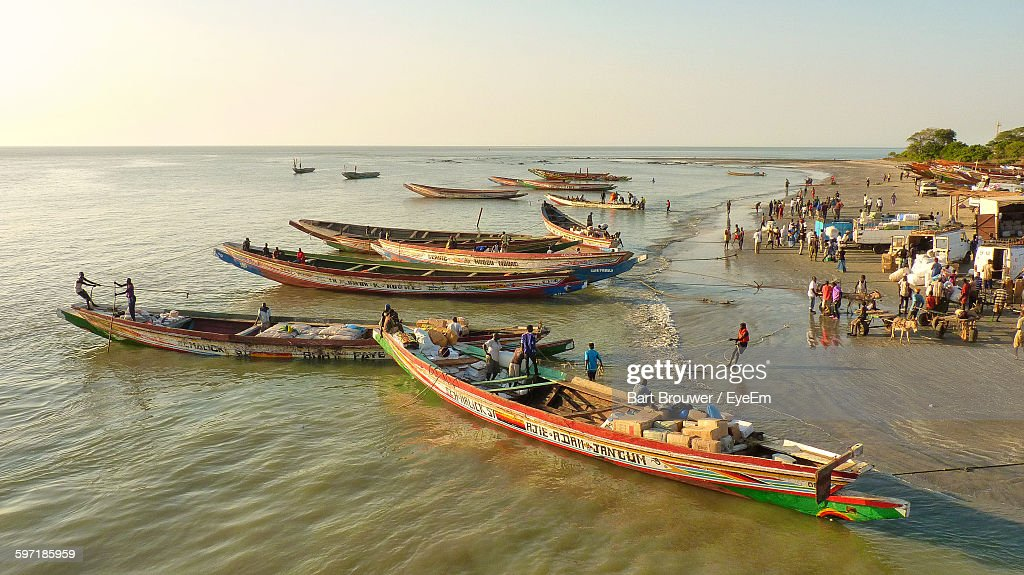 People With Boats At Gambia River Against Clear Sky : Stock Photo