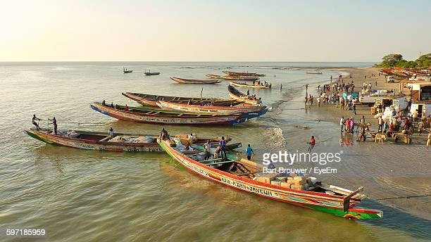 People With Boats At Gambia River Against Clear Sky